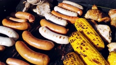 Grilling bratwursts and sausages, between chicken, pork and corn, on a gas ba Stock Footage