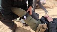 Iraq, February 2016: Man practicing putting on tourniquet on soldier's leg Stock Footage