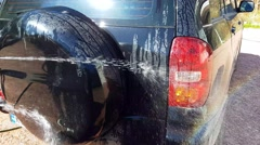 Washing a sport utility vehicle, on a home yard Stock Footage