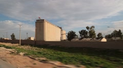 Driving by large silo in Iraq Stock Footage