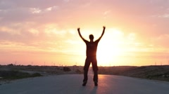 Man jumping and celebrating in front of a sunset Stock Footage