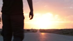 Man walking toward the camera with sunset and raises arms in victo Stock Footage