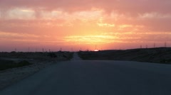 Sun going below the horizon with road in foreground - stock footage