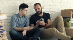 Father and son with smartphones talking about new home project on floor at their Stock Footage