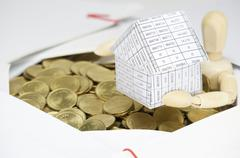 Close up wooden dummy holding house surrounded by gold coins Stock Photos