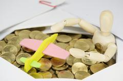 Airplane and wooden dummy surrounded by stack of gold coins - stock photo