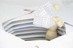 Wooden dummy holding house have surrounded by overload of paperwork - stock photo