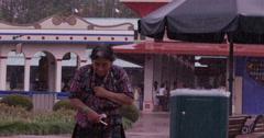 Tourist running in amusement park on a rainy day, Guatemala Stock Footage
