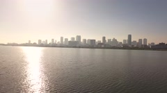 Climbing Aerial view of Skyline city over beautiful water in the morning sun Stock Footage