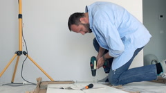 Young man matching pieces of furniture with drill on floor at home Stock Footage