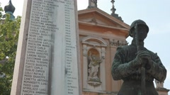 A soldier statue near a war memorial blessed by a Saint statue in Italy Stock Footage