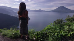 Girl standing on top of hill and looking at lake - stock footage