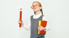 Schoolgirl child 7-8 years old with glasses holding books and a big pencil Stock Footage