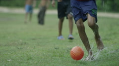 Group of boys playing football on a rainy day Stock Footage