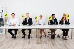 Happy Businesspeople Holding Voting Paper In Conference - stock photo