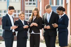 Group Of Multi-racial Businesspeople Using Mobile Phones;Outdoor Stock Photos