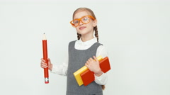 Schoolgirl 7-8 years old with glasses holding books and a big pencil. Child Stock Footage