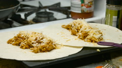 Putting cheese on chicken tacos in a kitchen Stock Footage