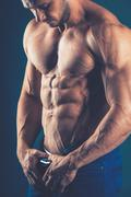 strong athletic man  on black background. To pump the abdominal - stock photo