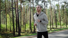 Man running looking at his pulse outside in nature on road with smartwatch. - stock footage