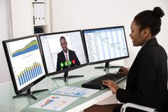Young African Businesswoman Working With Multiple Computer Screen Stock Photos