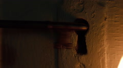 Skeleton key inserted in door by candlelight Stock Footage