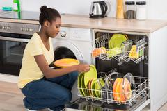 Happy Young Woman Arranging Plates In Dishwasher At Home - stock photo