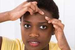 Close-up Of Young African Woman Looking At Pimple On Forehead Stock Photos
