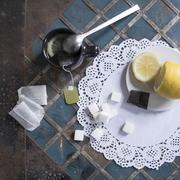 Cup of tea with lemon and sugar on lace doily Stock Photos