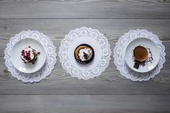 Plates of dessert on lace doilies Stock Photos