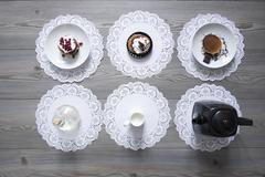 Teapot and plates of dessert on lace doilies Stock Photos