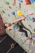 Mother belaying daughter climbing rock wall Kuvituskuvat