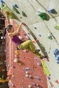 Japanese woman climbing rock wall Kuvituskuvat