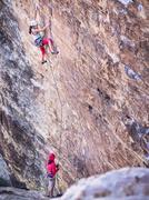 Mother belaying daughter rock climbing on cliff Kuvituskuvat