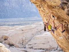 Mixed race girl rock climbing on cliff Kuvituskuvat