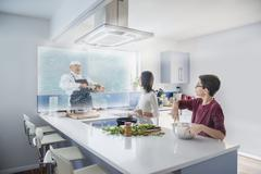 Brother and sister watching hologram cooking show in kitchen Stock Photos