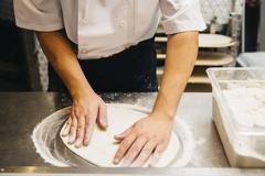 Chef shaping pizza dough in restaurant kitchen Stock Photos