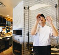 Chef tossing pizza dough in restaurant in kitchen Kuvituskuvat