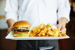 Caucasian waiter holding plate of cheeseburger and chips Stock Photos
