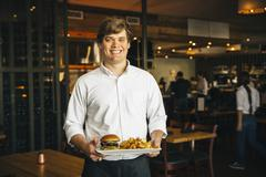 Caucasian waiter carrying cheeseburger and chips in cafe Stock Photos