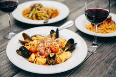 Plates of seafood and pasta with wine glasses Stock Photos