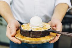 Caucasian waiter holding skillet dessert Stock Photos