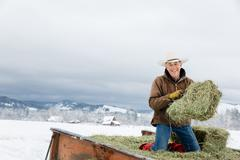 Caucasian farmer hauling hay in snowy field Stock Photos