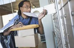 Black man gathering mail from post office box Stock Photos