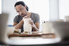 Black artist shaping ceramic vase in studio Stock Photos