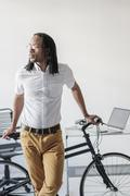 Black businessman with bicycle in office Stock Photos