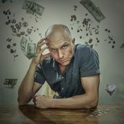Caucasian man sitting in falling money Stock Photos