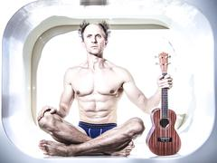 Caucasian musician holding ukulele in small alcove Stock Photos