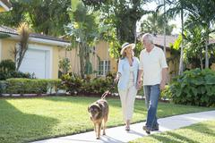 Caucasian couple walking dog in neighborhood - stock photo