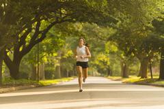 Caucasian woman jogging on neighborhood street Stock Photos